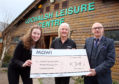 Kendal Hunter and Heather O'Neill of Mowi present half of the fundraising total to Paul Wood, chairman of the Lochalsh Leisure Centre