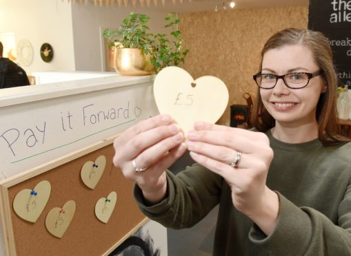 Claire Reed of The Alley Cat in Mealmarket Close in Inverness with their 'Pay it Forward' tokens.