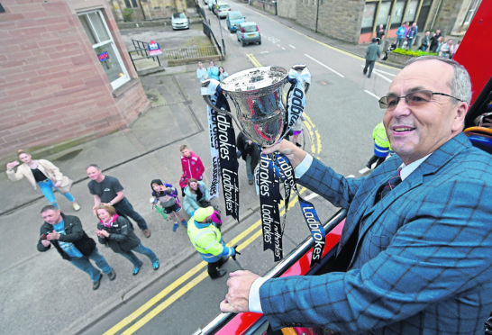 Chairman Roy MacGregor savours the moment with the trophy on the top deck of the bus.