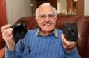 Fraserburgh Photographic Society's former president Andrew West with the Coronet Box Camera he took his first picture with in 1945 and his latest  lightweight digital camera
