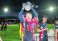 Ross County's Tom Grivosti holds aloft the Ladbrokes Championship trophy.