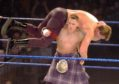 John Cena, wearing a kilt, lifts up Bradshaw in 2004