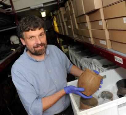 Picture from 2016 of University of Aberdeen Head of Museums Neil Curtis with a prehistoric beaker found in Chapelden
