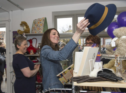 HOLT, UNITED KINGDOM - MARCH 18:  Catherine, Duchess of Cambridge tries on a Boden hat, priced at £15, as she takes a tour of the new EACH charity shop that she officially opened earlier today on March 18, 2016 in Holt, United Kingdom. (Photo by Arthur Edwards - WPA Pool/Getty Images)