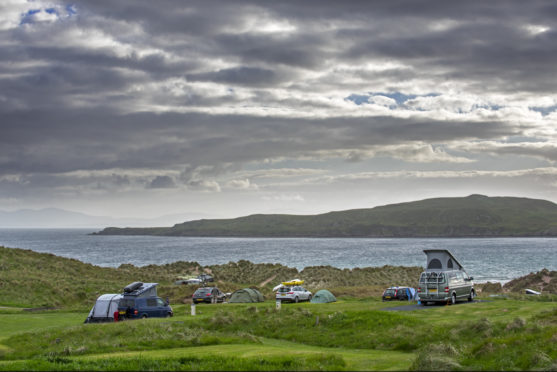 Campervans and tents on campsite along Loch Gairloch, Wester Ross.
