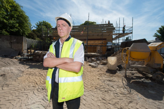 Picture by JASON HEDGES    Picture shows Design Consultant Colin T. Keir at the construction site of the new Co-op on the high street in Lhanbryde.
