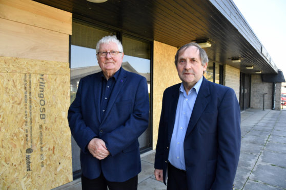 Councillors Norman Smith (l) and Jim Ingram at Mintlaw public library where vandals have smashed several full length windows.