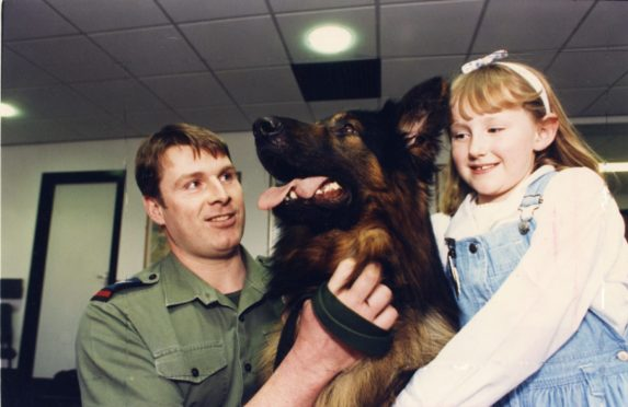 "Dr Gray's Hospital patient Fiona Urquhart, 7 cuddles RAF Police dog Banjo, held by Cpl Ian Booth."" Picture taken 27 March 1990."