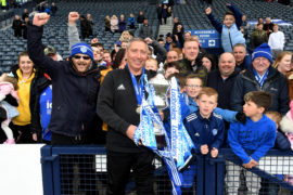 Peterhead manager Jim McInally celebrates with the Ladbrokes League 2 trophy and fans.