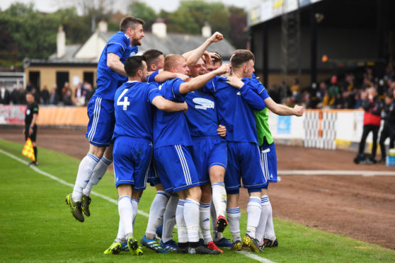 Cove players celebrate with Jordon Brown after his goal.