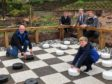 Committee member Ian Garden and grandson Callum playing the first game on the board watched by, left to right, Robert Stephen of Celebrations of Turriff, councillor Iain Taylor and Friends of Turriff Cemetery founder Fraser Watson