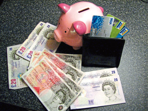 File photo dated 02/01/07 of a piggy bank, money notes and a wallet containing credit cards. Experts have claimed that a study shows money does not buy you happiness. PRESS ASSOCIATION Photo.