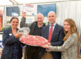 Archie collecting the tropy ,with left, Kate Rowell, chairman of Quality Meat Scotland, and to the right Jonathan Forses, from Kepak Group and Hannah Donegan from Tesco.