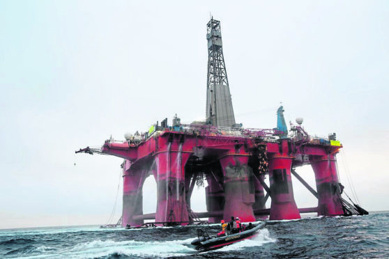 Greenpeace activists alongside the BP-chartered Transocean 'The Paul B Loyd Jr' rig en route to the Vorlich field in the North Sea. The rig is owned by Transocean, and on its way to the Vorlich field where it was to be drilling new oil wells, operated by BP, paying £140,000 a day for its use. BP is the operator, Transocean the owner, the same as the Deepwater Horizon. Greenpeace are calling on BP to halt drilling for new oil in light of climate emergency and refocus their business on renewable energy.