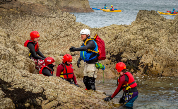 Chris McCann leading a coasteering group on behalf of Outfit Moray