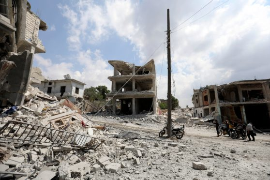 People gathering next to a damaged building in the town of Ihsim, in war-torn Syria's Idlib region