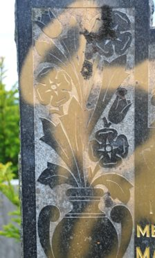 Graves have been daubed with paint in Elgin.