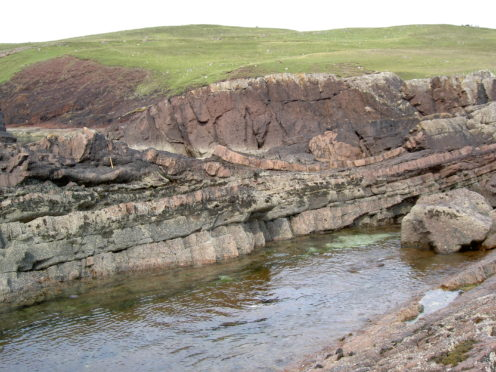 "A field photo take at Stoer showing the laminar beds of sandstone in the bottom of the picture. In the middle is the impact deposit (12m thick at this location) that contains ""rafts"" of deformed pink sandstone."