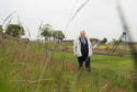 Councillor James Allen is pictured at Lossiemouth playing fields at the site of where the grass has now been cut.