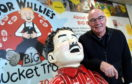 CR0010263 Former Dons captain Willie Miller visited the Oor Wullie Bucket Trail shop in the Bon Accord centre today (wednesday) to sign the sculpture by artist Sarah Mauchline that will be displayed and auctioned for the Archie Foundation.        Pictured - Willie Miller with the Oor Wullie Miller statue.       Picture by Kami Thomson    12-06-19