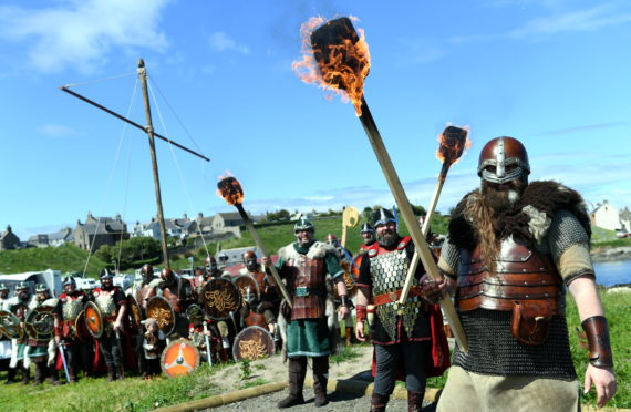 L-R Guizer Jarl's, Keith Poleson, Neil Pearson and Lyall Gair holding torches in front of their squad.         Picture by Kami Thomson