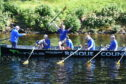 Delight as the crew of the safety boat relay back to the band of hardy rowers that their efforts have set a new record time for navigating Loch Ness in a rowing boat. Picture by Sandy McCook