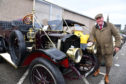 Owner Alfie Cheyne polishes the brass headlamps on his 1910 Whye steam car.