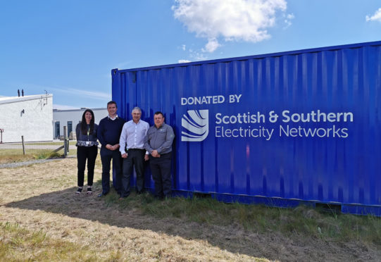 Pamela Harvey, Angus Brendan MacNeil, Paul Schofield and CJ MacPhe at the container donated to the kayaking club.