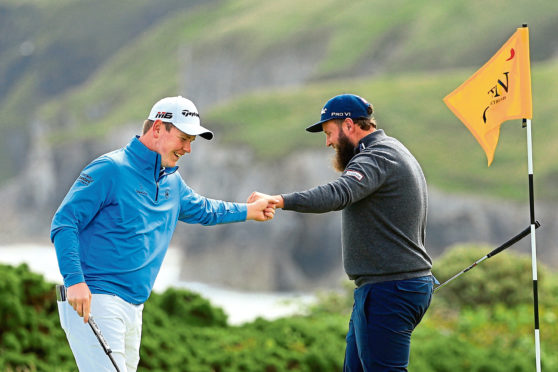PORTRUSH, NORTHERN IRELAND - JULY 18: Andrew Johnston of England high fives Robert MacIntyre of Scotland on the 5th green during the first round of the 148th Open Championship held on the Dunluce Links at Royal Portrush Golf Club on July 18, 2019 in Portrush, United Kingdom. (Photo by Mike Ehrmann/Getty Images)