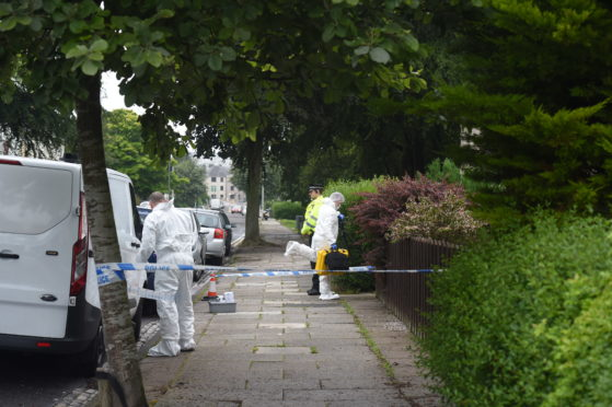 Police and forensics officers at the property in Clifton Road, Aberdeen. Photograph by Heather Fowlie