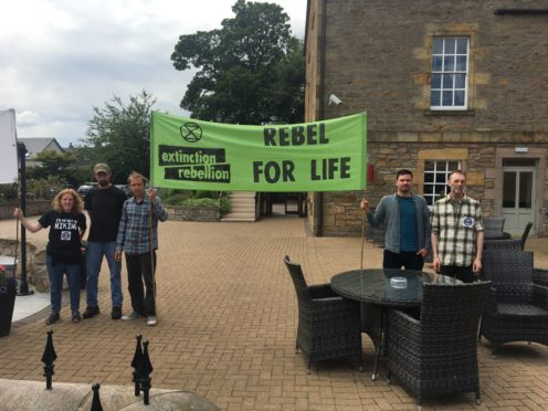 Extinction Rebellion campaigners protesting outside Mansefield Hotel in Elgin