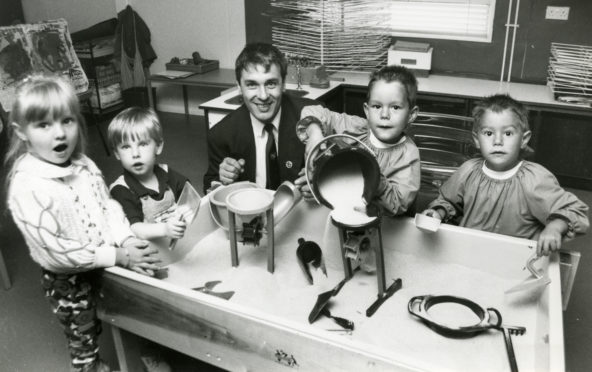 """Councillor Brian Topping joins pupils (from left) Stacey McBride, John Downie and twin brothers John and Jason Jappy at the sandpit."""" From August 1992"""