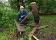 Eric Marriott is pictured in the forest area with a broken bench.