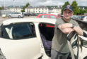 Damian Tucker with his car which was flooded out as it sat in his garage off Strathpeffer Road.