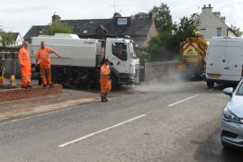 Workmen clearing the remaining water from the roads.