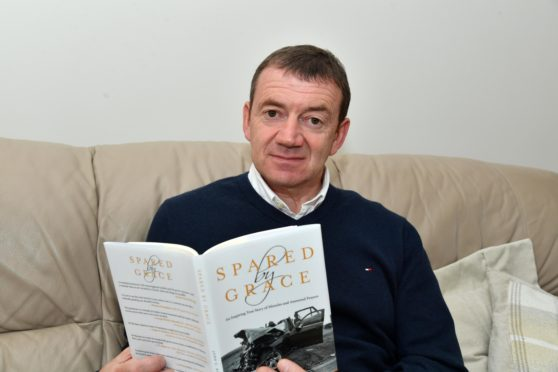 JOHN BUCHAN WITH HIS BOOK DETAILING THE HORRIFIC INJURIES HE RECEIVED IN A CAR CRASH IN 2014.