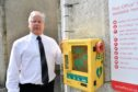 Councillor John Cox beside the defibrillator box in Aberchirder which was vandalised and broken.