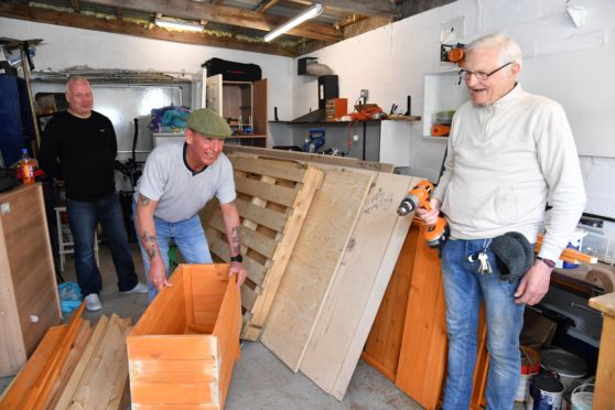 Ian Thomson (L), Len Steel and David Innes working in the cramped conditions at the Fraserburgh Men Shed.