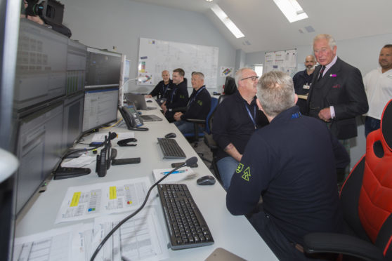 Prince Charles chats with marine co-ordinator Colin Brown and Gordon Morrison in the Beatrice Offshore Windfarm control room at Wick Harbour.