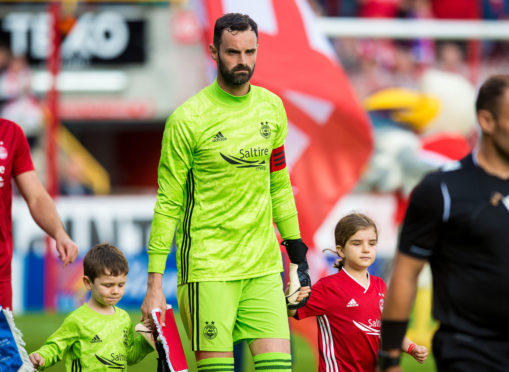 Aberdeen captain Joe Lewis leads his team out onto the field.