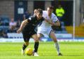 Aaron Doran holds off Dundee's Jordan McGhee.