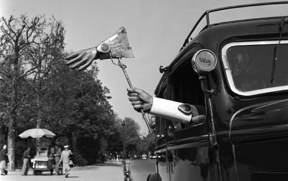 1955:  French taxi driver Pierre Alidiere has won accolades for his range of inventions, including this 'trafficator' glove which lights up to indicate that his cab is turning.  (Photo by Vagn Hansen/BIPs/Getty Images)