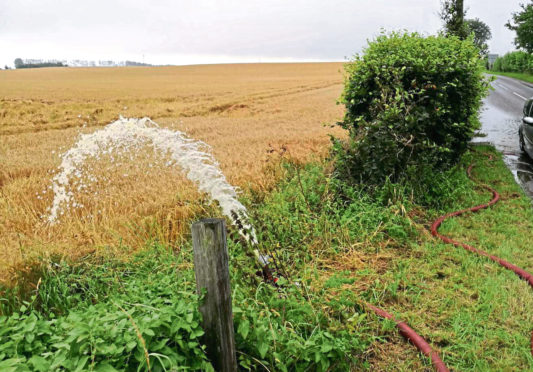 Water being pumped from a flooded house into a field of spring barley.