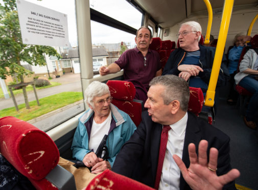 Highlands and Islands MSP David Stewart talks to passengers on the bus.