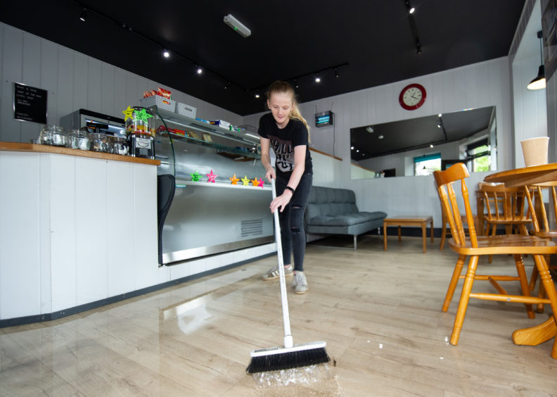 Toni Smith from Bean and Gone is pictured sweeping away water.