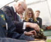 Deputy First Minister John Swinney yesterday visited Nairn Academy and the Farmer Jones Academy for pupils at the school. John Swinney, helped by pupils, plants a pumpkin the polytunnel. Picture by Sandy McCook