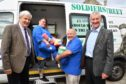 MSPs Maurice Corry (l) and Peter Chapman watch Privates on Parade volunteers Elaine Mitchell and James Grieve loading sleeping bags, blankets and hygiene kits destined for homeless veterans.