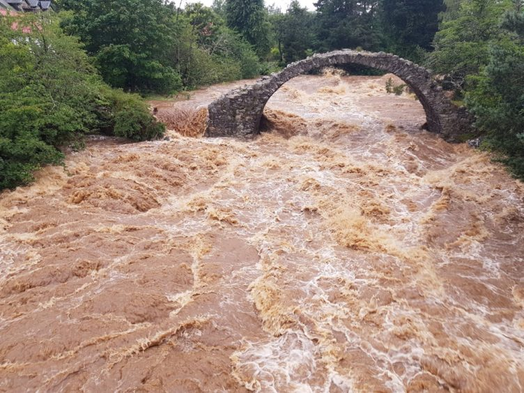 WATCH: Torrential rain causes flooding at the Highlands oldest stone bridge