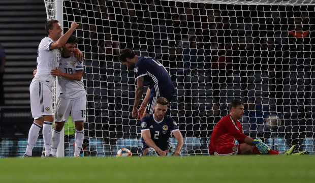 Stephen O'Donnell looks on as Yuri Zhirkov celebrates Russia's second goal.
