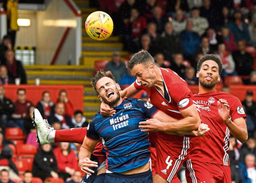 Aberdeen's Andrew Considine (C) competes with Keith Watson for the ball during the Ladbrokes Premiership match between Aberdeen and Ross County at Pittodrie Stadium on August 31